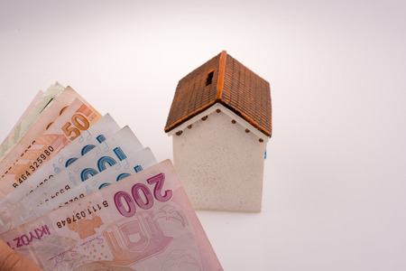 Turkish Lira banknotes by the side of a model house on white background