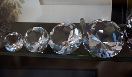 Five transparent diamonds aligned from small to big on display 스톡 콘텐츠