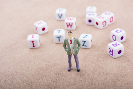 Figurine standing in front of the colorful alphabet letter cubes 写真素材