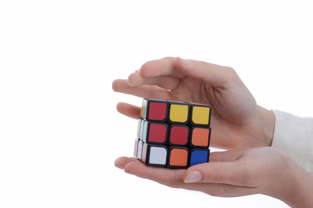 Child holding a Rubik's cube in hand on a white Editorial