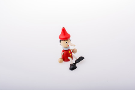 Wooden pinocchio doll with his long nose on a white background Banco de Imagens - 121480546
