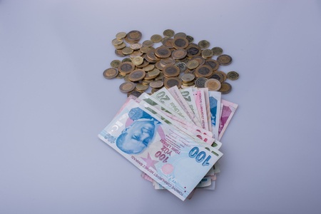 Turkish Lira coins and banknotes side by side on white
