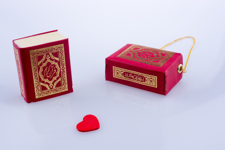 The Holy Quran with a heart on a white