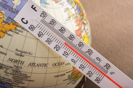Hand placing a thermometer on a little model globe