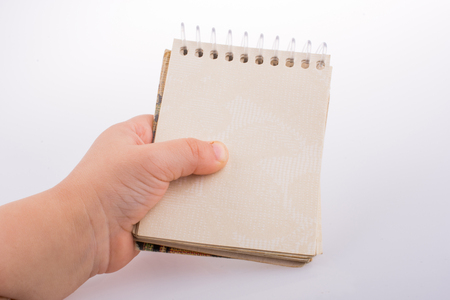 Baby holding a Spiral blank notebook on a white Imagens