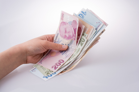 Hand holding Turkish Lira banknotes on white