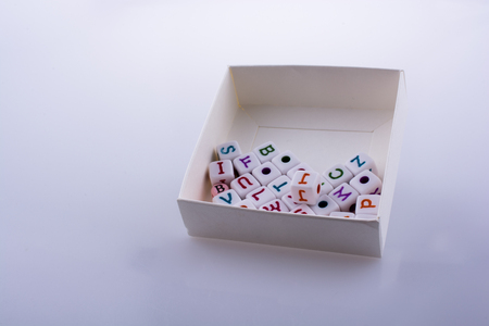 Colorful alphabet letter cubes in a box on a white