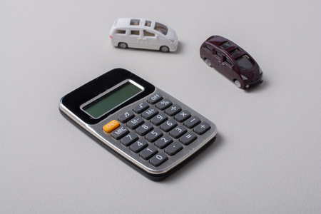 Little size cars beside a calculator on white Stok Fotoğraf