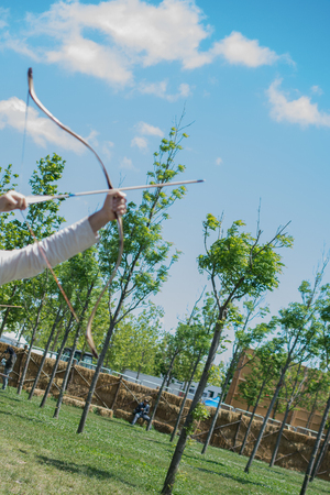 Archer with bow  in traditional clothes shooting an arrow