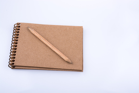 Pencil placed on a notebook on a white