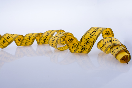 Yellow color measuring tape on a white