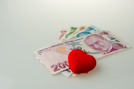 Turkish Lira banknotes by the side of a red color heart shaped object on white background
