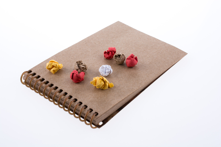 Colorful crumbled paper on a notebook on a white background