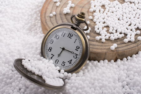 Retro pocket watch on white polystyrene balls