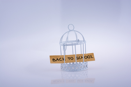 Little note about school placed in a white color bird house with metal bars