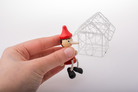Hand holding pinocchio beside a white color model house Stock Photo - 121493468