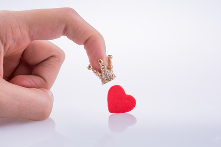 Hand holding crown near a red heart on a white background