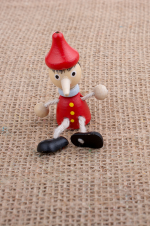 Wooden Pinocchio doll sitting on canvas background 版權商用圖片