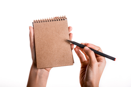 Spiral brown notebook with a pen held by a child on a white background