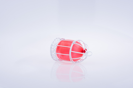 Little red balloon placed in a white color bird house with metal bars