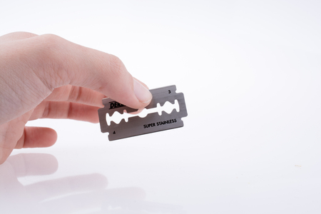 Hand holding a razor blade on a white background Banque d'images