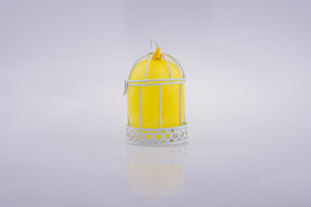 Little yellow balloon placed in a white color bird house with metal bars Imagens
