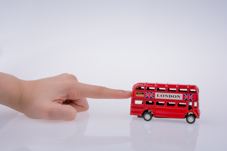 Child hand playing with London double decker bus  model on white background