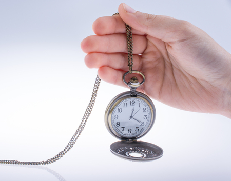 Mano sosteniendo un reloj de bolsillo de estilo retro en la mano Foto de archivo
