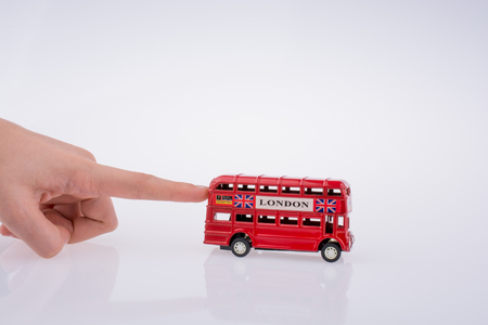 Child hand playing with London double decker bus  model on white background Stockfoto - 121494332