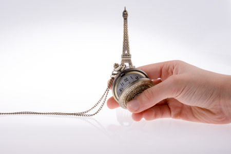 Hand holding a pocket watch befere Eifel Tower Stock Photo
