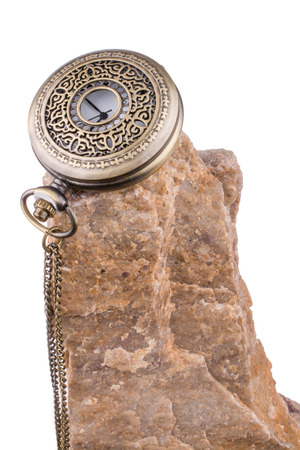 Pocket watch on the top of a rock on a white background