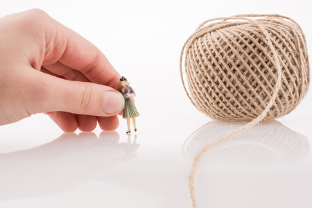 Woman figure beside a linen spool of thread on a white background Standard-Bild - 121707374