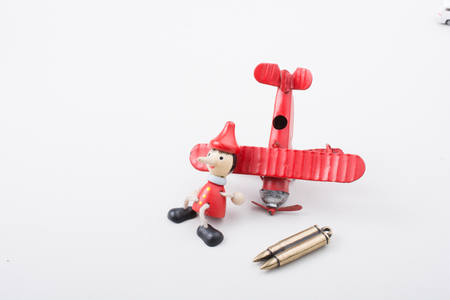 Airplane, Bullet and wooden pinocchio with his long nose Stock Photo