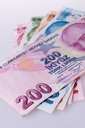 Turkish Lira banknotes by the side of a red color heart shaped object on white background Stock fotó