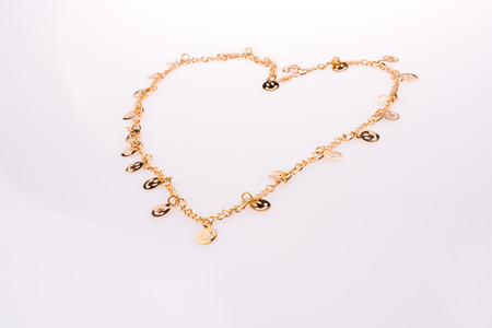 Golden color smileys arrayed on a chain in hands form a heart shape