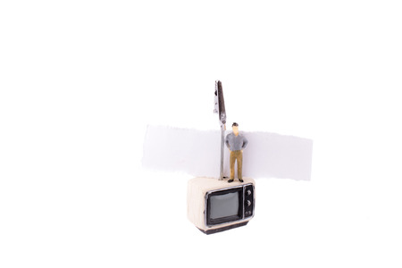Man standing on the top of a retro styled television set with a piece of paper on a white background Banco de Imagens - 121532847