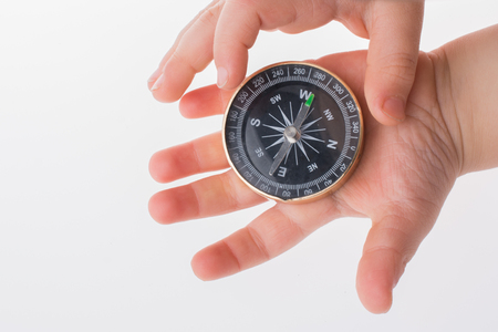 Child hand holding a compass  on a white background Фото со стока