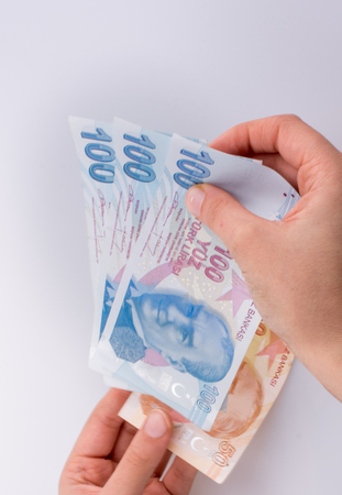 Hands holding Turksh Lira banknotes by the side of American dollar banknotes on white background