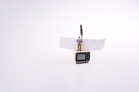 Man standing on the top of a retro styled television set with a piece of paper on a white background