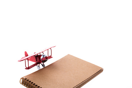 Airplane and notebook on white background