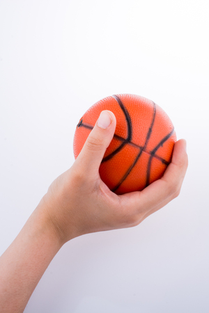 Hand holding an orange basketball model on a white background