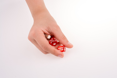 Hand holding red dice on a white background Фото со стока