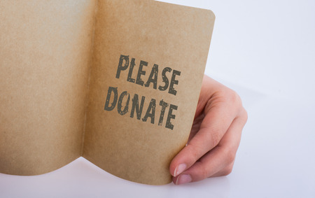Hand holding a sheet of paper   with please donate wording Stock Photo