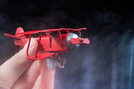 Hand holding a red toy plane on a black Stock Photo