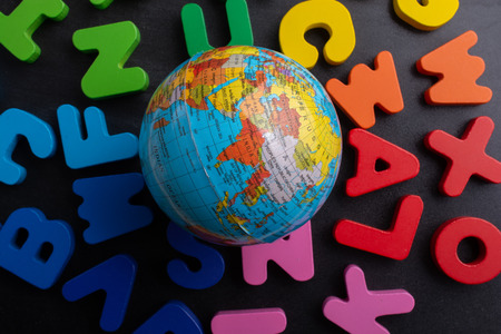 Earth globe model on colorful letters on a black Stock Photo