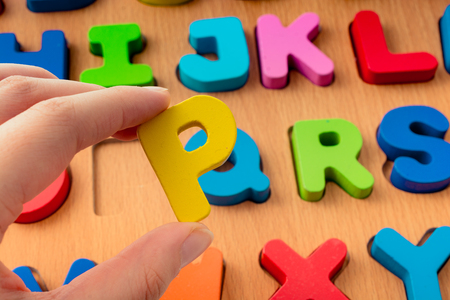 Colorful Letter of Alphabet P made of wood in hand