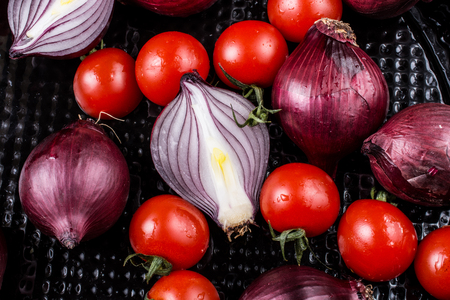 Cherry tomatoes and purple onions in a black tray Stock Photo