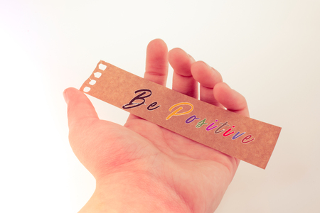 Hand holding torn notepaper with  be Positive thinking concept label