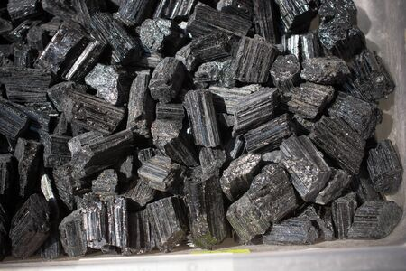 Natural rock specimen - raw crystal of black Tourmaline (Schorl) gemstone Stock Photo