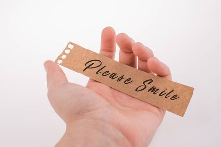 Please smile text on paper on a white background Imagens